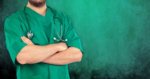 Close up of a doctor with his arms crossed. On green background Stock Photo