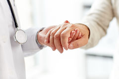 Close up of doctor holding old man hand stock photography
