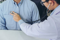 Close up of doctor listening to patient heartbeat with stethosco. Pe on hospital, Physical examination, Medical and health care concept Royalty Free Stock Image
