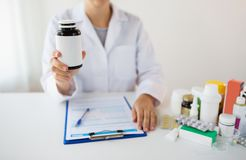 Close up of doctor with medicines and clipboard Stock Photography
