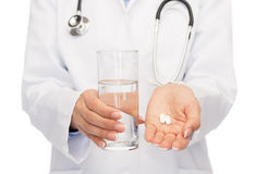 Close up of doctor offering pills and water Royalty Free Stock Images