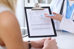 Close up of a doctor and  patient hands while phisician pointing into medical history form at clipboard Stock Photos