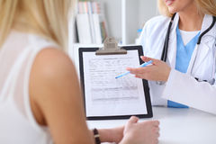 Close up of a doctor and  patient hands while phisician pointing into medical history form at clipboard Stock Photo