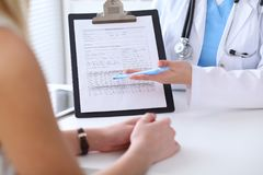 Close up of a doctor and  patient hands while phisician pointing into medical history form at clipboard Royalty Free Stock Photos