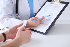 Close up of a doctor and patient hands while phisician pointing into medical history form at clipboard. Medicine and health care concept stock photo
