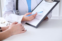 Close up of a doctor and  patient hands while phisician pointing into medical history form at clipboard Royalty Free Stock Photography