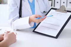 Close up of a doctor and  patient hands while phisician pointing into medical history form at clipboard Stock Images
