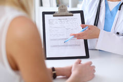 Close up of a doctor and  patient hands while phisician pointing into medical history form at clipboard Royalty Free Stock Photo