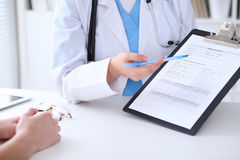 Close up of a doctor and  patient hands while phisician pointing into medical history form at clipboard Royalty Free Stock Images