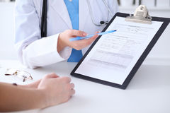 Close up of a doctor and  patient hands while phisician pointing into medical history form at clipboard Stock Photography