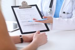 Close up of a doctor and  patient hands while phisician pointing into medical history form at clipboard Stock Image