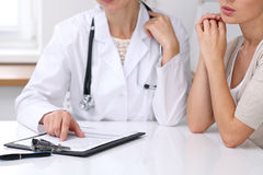 Close up of doctor and  patient  sitting at the desk while physician pointing into medical form hystory. Medicine a Royalty Free Stock Image