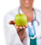 Close-up of a doctor presenting a green apple Royalty Free Stock Image