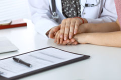 Close-up of doctor  reassuring her female patient. Medical ethics and trust concept Stock Images