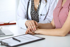 Close-up of doctor  reassuring her female patient. Medical ethics and trust concept Stock Photo