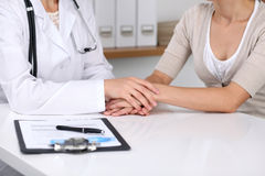 Close up of a doctor reassuring her female patient while  sitting at the desk. Medicine, help and health care concept Stock Photos