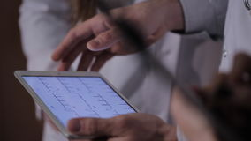 Close-up of doctor`s hands, considering the patient`s cardiogram on the tablet. stock video