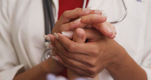 Close up of doctor's hands holding patient's hand Stock Image