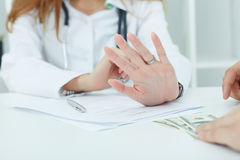 Close-up of doctor`s hands refusing a bribe. Royalty Free Stock Image