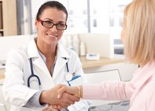 Close up of doctor shaking hands with patient Royalty Free Stock Image