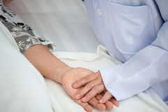 Close-up Doctor take care hold hand patient grandmother sleep in elderly Home stock images