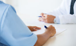 Close up of doctor taking notes at hospital Stock Photos