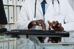 Close-up Of Doctor Typing On Keyboard Royalty Free Stock Images
