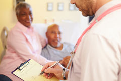 Close Up Of Doctor Updating Patient Notes Stock Image