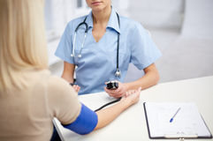 Close up of doctor and woman measuring pressure Royalty Free Stock Photos