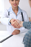 Close up of a doctor woman shaking hands with her male patient. Medicine and trust concept.  Stock Images