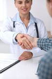 Close up of a doctor woman shaking hands with her male patient. Medicine and trust concept. Close up of a doctor women shaking hands with her male patient Royalty Free Stock Image
