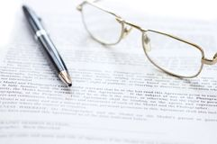 Close-up of document, eyeglasses and pen. Stock Image