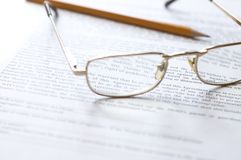 Close-up of document, eyeglasses and pencil. Stock Photography