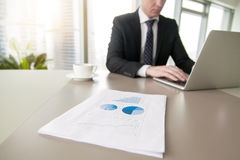 Close up of a document with statistics. Close up of paper financial document with statistics, man dealing with business problems and the technology solutions stock photography