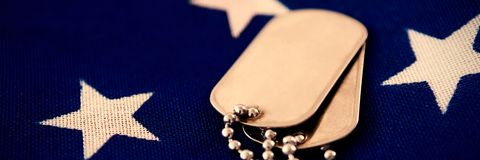 Close-up of dog tag pendant on flag Royalty Free Stock Photos