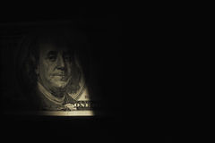 Close up of dollar bill in shadow as a symbol of hidden profits Royalty Free Stock Images