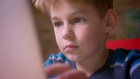 Close-up dolly shot of cute small boy working with laptop being concentrated at home. stock footage