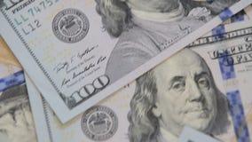 Close up dolly shot of scattered American paper money bills. Cash money background. Benjamin Franklin portrait on 100 US dollar bi. Ll close up stock video