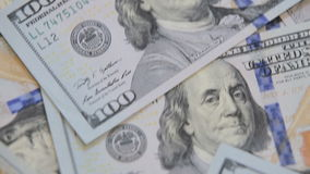 Close up dolly shot of scattered American paper money bills. Cash money background. Benjamin Franklin portrait on 100 US dollar bi. Ll close up stock video footage