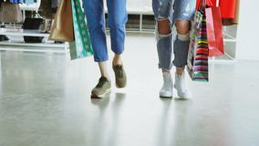 Close-up dolly shot of women`s legs walking slowly through luxurious shop. Women are wearing jeans and trainers and stock video