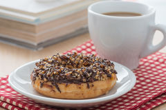 Close up, Donut chocolate with nut topping and a cup of coffee. Stock Images