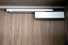 Close up of a door closer. Hotel or home exterior doors stock images