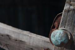 Close up of door knob on broken door. Close up of broken metal door knob on abandoned shed door Stock Image