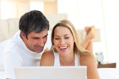 Close-up dos amantes que usam um portátil que encontra-se na cama Imagem de Stock