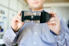 Close up dos auriculares da realidade virtual nas mãos do homem imagens de stock royalty free