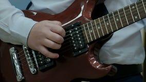 Close-up dos dedos de um adolescente que joga uma guitarra elétrica marrom O indivíduo puxa as cordas em uma ferramenta elétrica  video estoque