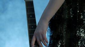 Close-up dos dedos fêmeas Uma menina em um vestido do concerto aproxima o pescoço da guitarra e passa-a delicadamente para ceder  vídeos de arquivo