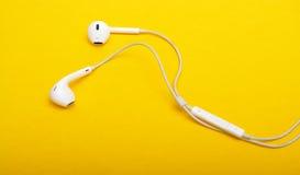 Close up dos fones de ouvido no fundo amarelo Foto de Stock Royalty Free
