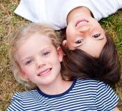 Close-up dos irmãos bonitos que encontram-se na grama foto de stock royalty free