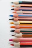 Close-up dos lápis coloridos arranjados em seguido Fotografia de Stock Royalty Free